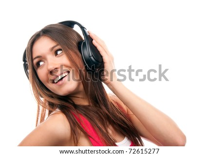 Attractive cheerful brunette woman listening and enjoying music in headphones, smiling, laughing and not looking in camera isolated on a white background