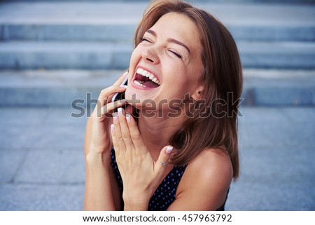 Attractive cheerful female is speaking on the phone and laughing sincerely over grey street stairs background - stock photo
