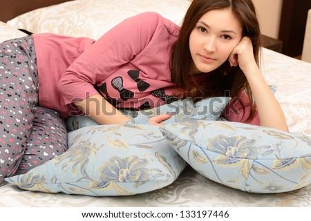 attractive cheerful teen girl in pajamas lying in her bedroom - stock photo