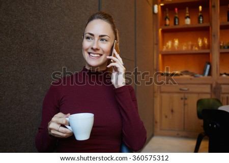 Attractive cheerful woman speaking on mobile phone with friend while enjoying cup of cappuccino in modern cafe, young businesswoman have nice talking conversation on cell telephone during work break - stock photo