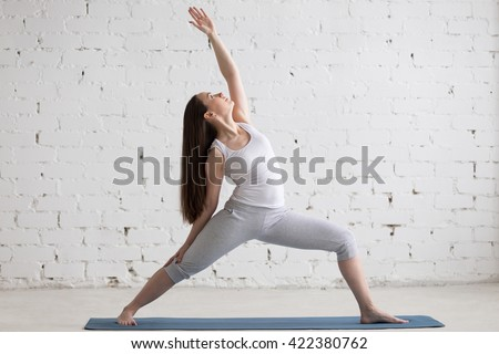 Attractive cheerful young woman working out indoors. Beautiful model doing exercises on blue mat in room with white walls. Peaceful or Reverse Warrior Pose, Viparita Virabhadrasana. Full length - stock photo