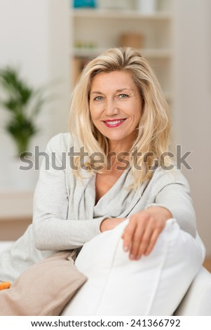 Attractive confident middle-aged woman relaxing on her sofa looking at the camera with a friendly charming smile - stock photo