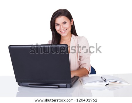 Attractive confident young professional woman sitting working at her laptop with an open book alongside her