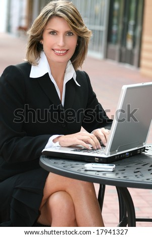 Attractive corporate, business woman working on her laptop outdoors, in a city street