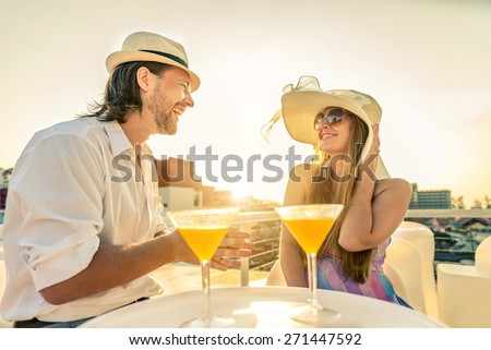 Attractive couple at party talking and having fun in a cocktail bar - Two young persons drinking aperitif at sunset in a luxurious hotel - stock photo