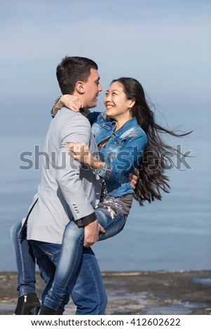 Attractive couple at the sea. European guy carrying  his asian girl