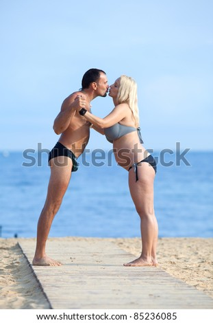 Attractive couple at the sea. Middle aged man and young pregnant woman on the beach - stock photo