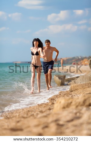 Attractive couple at the sea. Young man and woman running along pebble beach