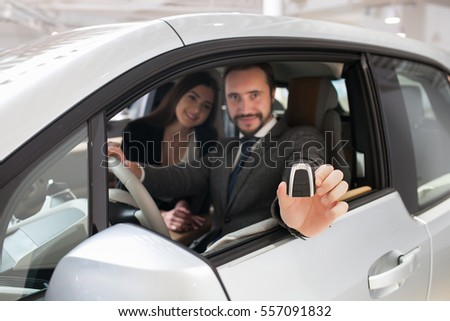 Attractive couple chooses a new car in the showroom