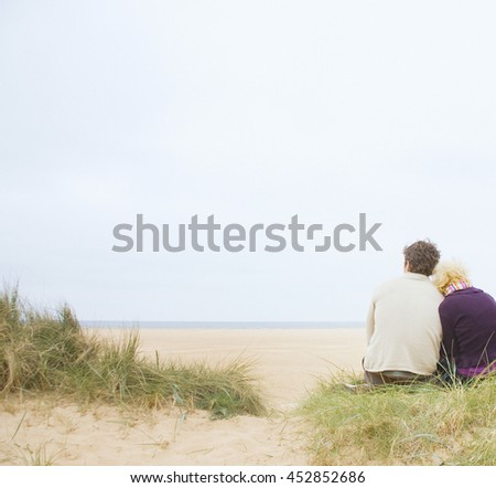 Attractive couple cuddling at the beach - stock photo
