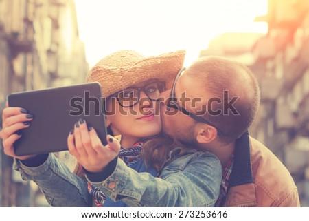 Attractive couple doing selfie outdoors. - stock photo