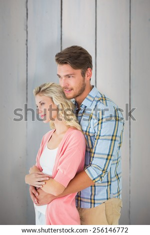 Attractive couple embracing and smiling against painted blue wooden planks - stock photo