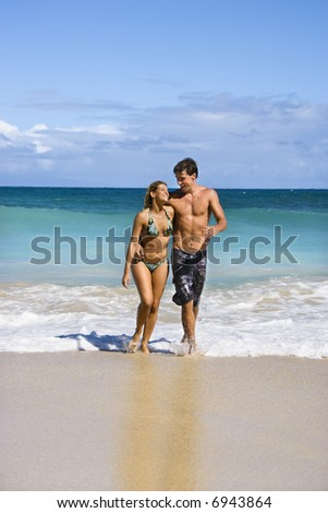Attractive couple embracing and smiling as they walk out of water in Maui, Hawaii.