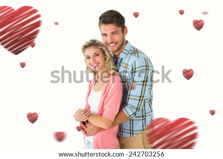 Attractive couple embracing and smiling at camera against hearts - stock photo