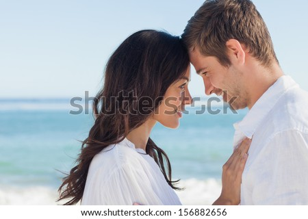 Attractive couple embracing on the beach on a sunny day - stock photo
