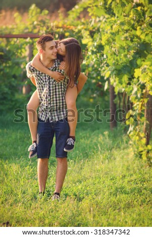 Attractive Couple Enjoying Romantic Sunset in the Countryside / with custom white balance, color filters, and some film grain added - stock photo