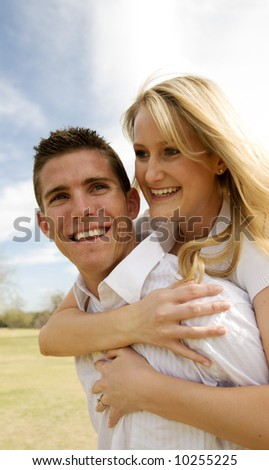 Attractive couple having fun while man gives woman a piggy back ride