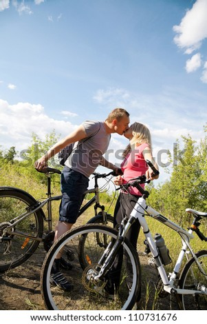 Attractive couple holding bicycles and kissing