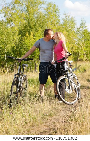 Attractive couple holding bicycles and kissing in green environment - stock photo