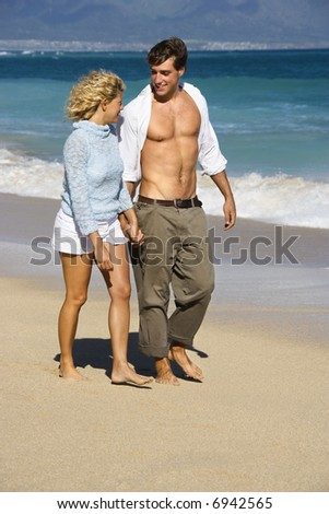 Attractive couple holding hands walking on beach smiling at eachother in Maui, Hawaii.