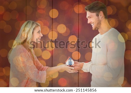 Attractive couple holding miniature house model against close up of christmas lights - stock photo
