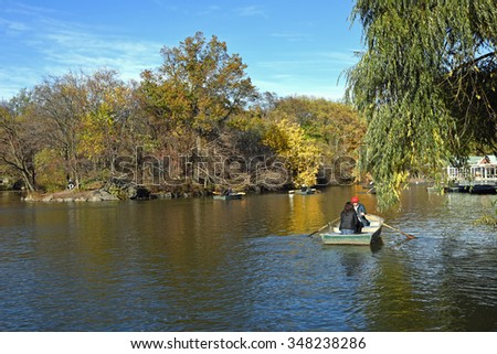 Attractive couple in a row boat  in Central Park, New York City. - stock photo