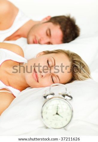 Attractive couple in bed with alarm clock going off - stock photo