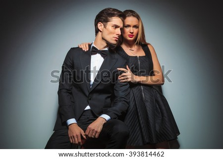 attractive couple in black posing in studio background, she looking at the camera while embracing him. man looks away from the camera.