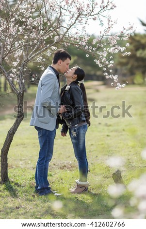 Attractive couple in blossoming park. Asian girl and european guy kissing against of blossoming almond trees