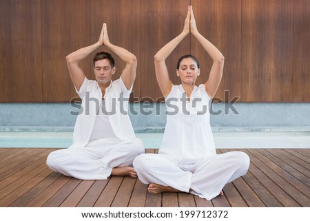 Attractive couple in white sitting in lotus pose with hands together in health spa - stock photo