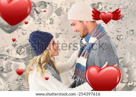 Attractive couple in winter fashion hugging against grey valentines heart pattern - stock photo