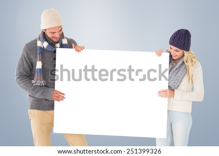 Attractive couple in winter fashion showing poster against grey vignette - stock photo