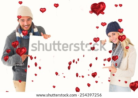 Attractive couple in winter fashion showing poster against red heart balloons floating - stock photo