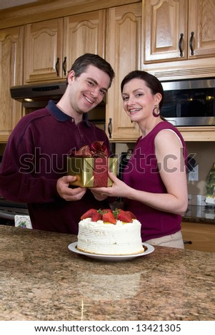 Attractive couple laughing at the camera while standing in the kitchen and exchanging gifts and cake. Vertically framed shot. - stock photo