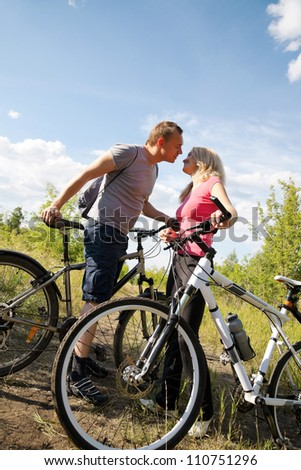 Attractive couple looking at each other with love during biking