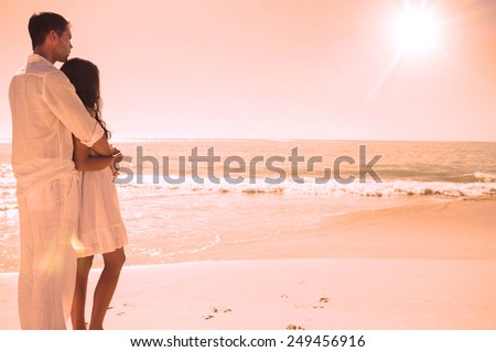 Attractive couple looking out at sea at the beach - stock photo