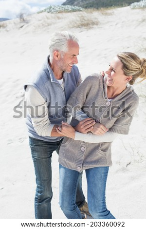 Attractive couple messing about on the beach on a bright but cool day - stock photo
