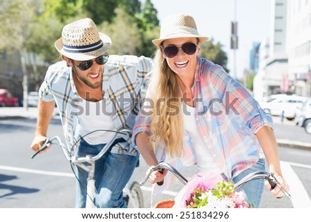 Attractive couple on a bike ride on a sunny day in the city - stock photo