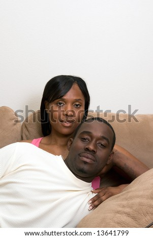 Attractive couple on a couch together. He is lying across her lap. Vertically framed photograph. They have a serious expression on their faces.