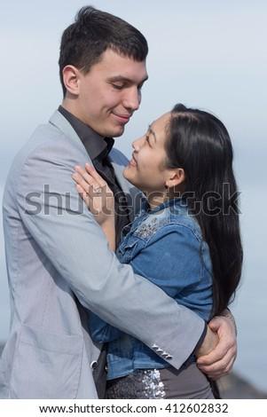 Attractive couple on open air. European guy embracing Korean girl - stock photo