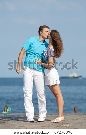 Attractive couple on pier. Young man and woman are kissing on background of sea