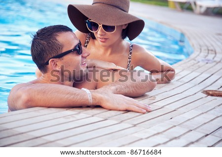 Attractive couple on poolside - stock photo