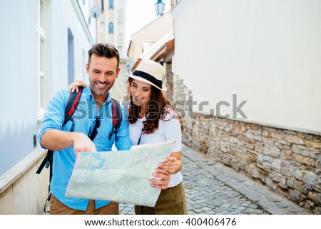 Attractive couple on vacation, sightseeing old town with map - stock photo