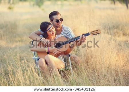 Attractive couple playing guitar, outdoors - stock photo