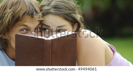 Attractive couple read together in the park - stock photo