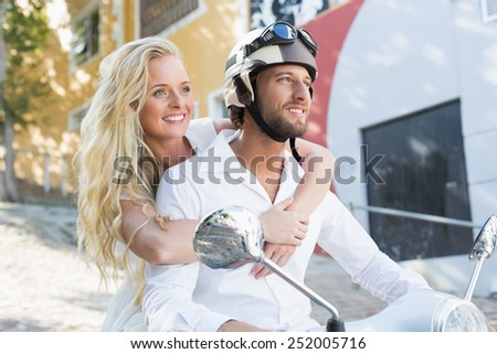 Attractive couple riding a scooter on a sunny day in the city - stock photo