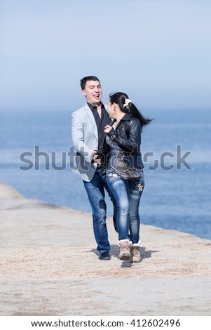 Attractive couple running along of pier. European guy catches his asian girlfriend - stock photo
