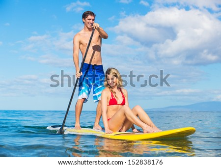 Attractive Couple Sharring Stand Up Paddle Board, Hawaii - stock photo