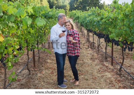 Attractive couple showing affection while holding wine glasses in a vineyard - stock photo