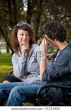 Attractive couple sitting on bench in the park